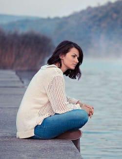 Image of girl sitting on lake side thinking
